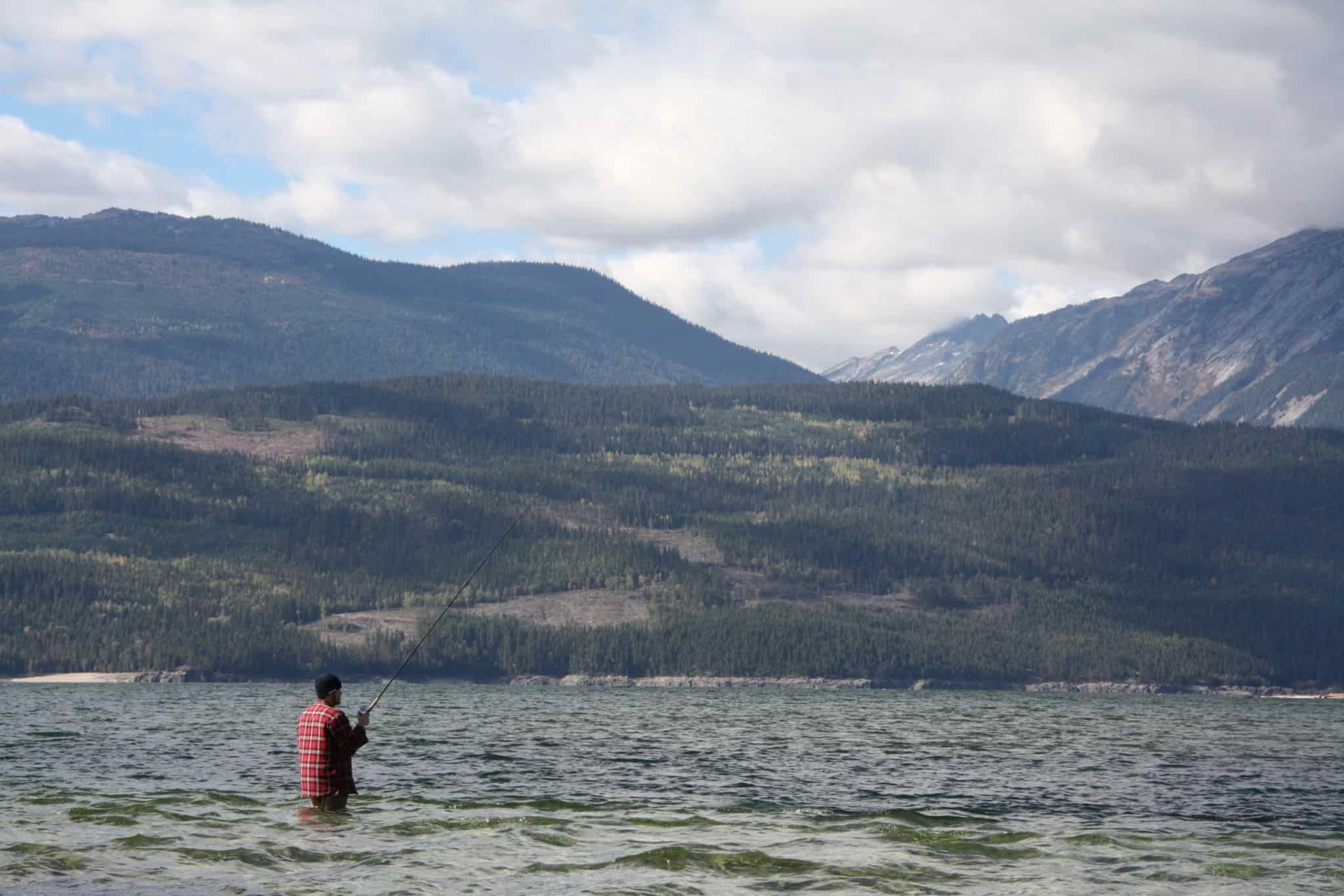 Man fishing wading in lake