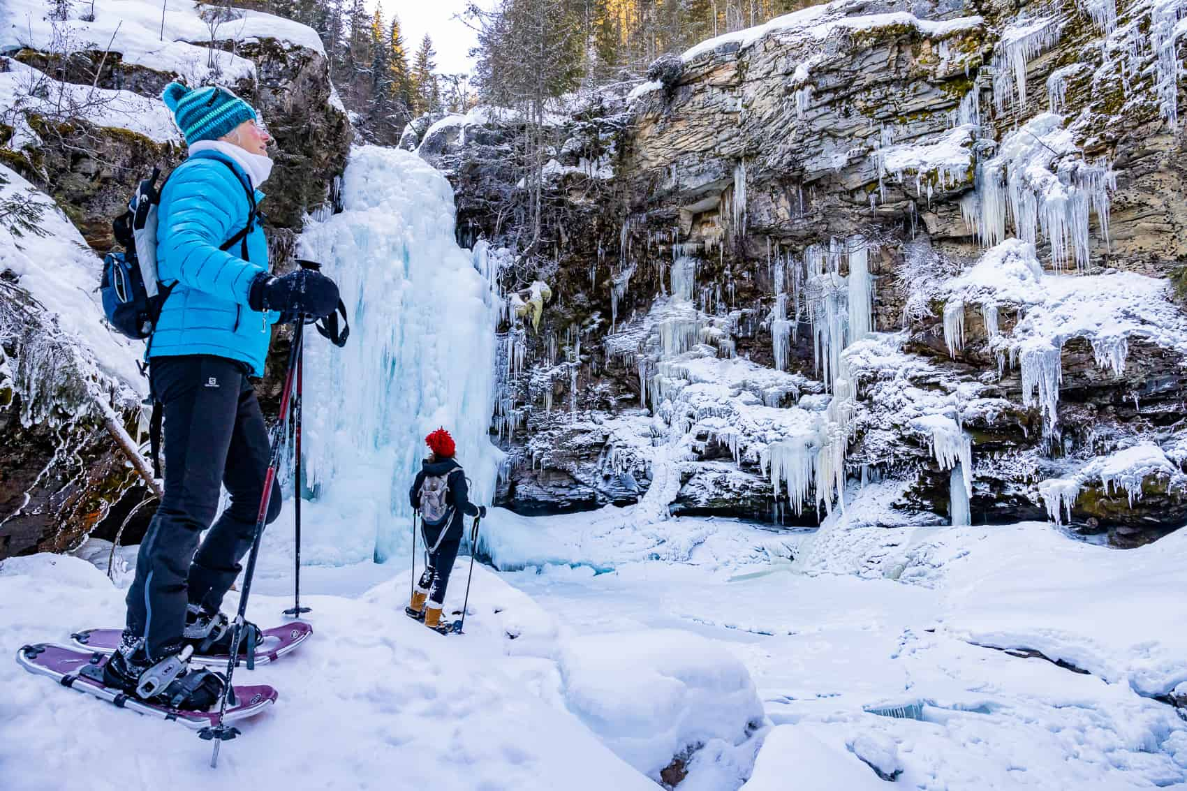 Snowshoeing near frozen waterfall Revelstoke